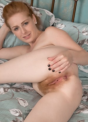 Tia Jones is playing around in her bedroom, and takes off her lingerie. She lays back, opens her legs, and shows her red hairy bush. She has a fire red hairy pussy and sexy pink pussy lips to love.